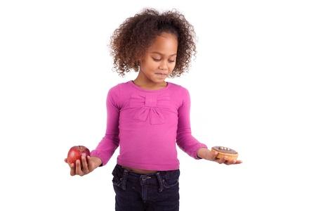 dudando: Ni�a africana asi�tica dudando entre frutas o dulces, aislados en fondo blanco