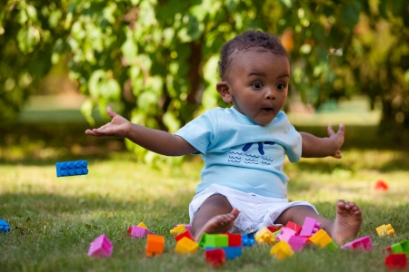 Portrait of a little african american baby boy playing outdoor in the grass photo