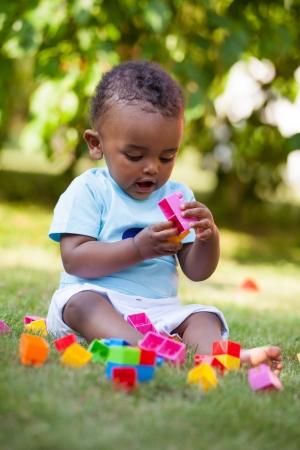 ni�os jugando en el parque: Retrato de un peque�o muchacho africano americano beb� jugando al aire libre en la hierba