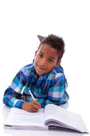 garcon africain: Petit gar�on africain couch�e sur le sol et livre de lecture, isol� sur fond blanc