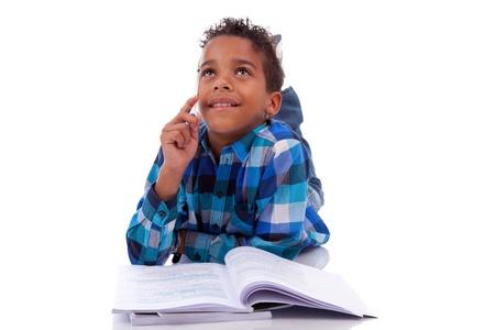 garcon africain: Petit garçon africain couchée sur le sol et livre de lecture, isolé sur fond blanc