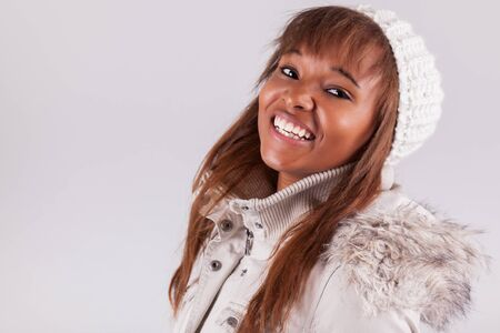 Young african american woman wearing winter clothes, isolated on white background Stock Photo - 17078462