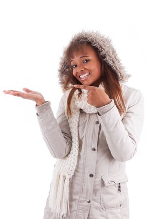 Young african american woman wearing winter clothes holding something in her hand, isolated on white background photo