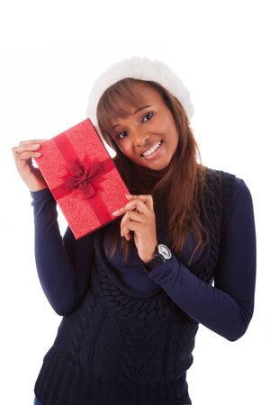 Young African American woman wearing a santa hat holding gift box, isolated on white background photo