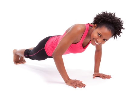 push people: Young beautiful african fitness woman doing push up exercises on floor,isolated on white background