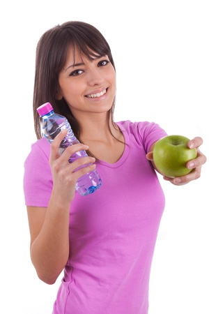 Young caucasian woman holding a bottle of water and an apple over white background photo