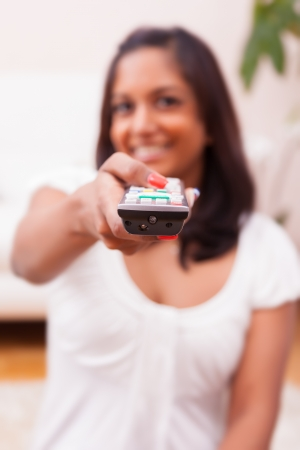 Young beautiful indian woman using a a tv remote controller photo