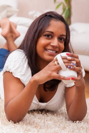 Young beautiful indian woman drinking coffee , lying on the floor while photo