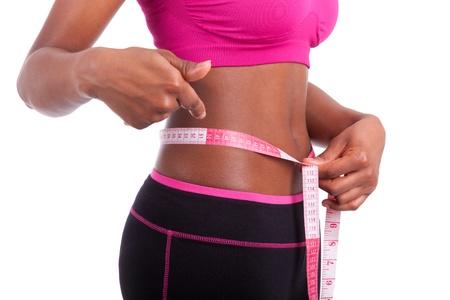 cintura perfecta: African American Fitness mujer que muestra su vientre, aislados en fondo blanco Foto de archivo