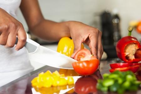 African American: Mano womans africano americano rebanar un tomate Foto de archivo