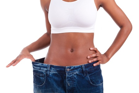 brazilian woman: Young african woman in old jeans pant after losing weight. Isolated on white background. Stock Photo