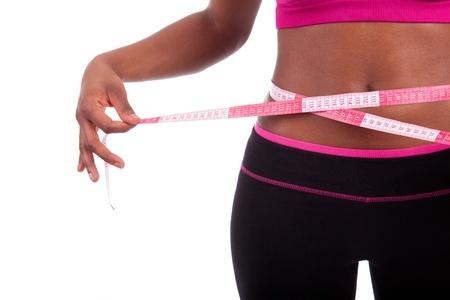 cintura perfecta: African American Fitness mujer que mide su vientre, aislados en fondo blanco