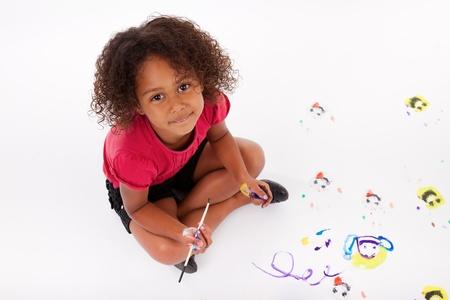 hand schilderen: Leuk Weinig Afrikaans Amerikaans meisje schilderij op de vloer Stockfoto