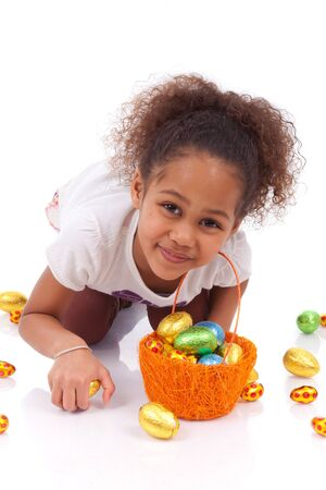 African Asian girl holding chocolate ester egg, isolated on white background photo