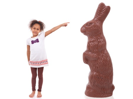 black giant: African Asian girl pointing a giant chocolate rabbit, isolated on white background