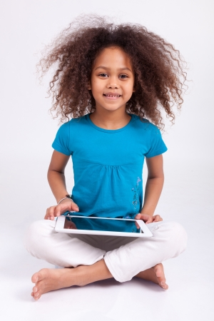 Little african asian girl using a tablet  pc, isolated on white background photo