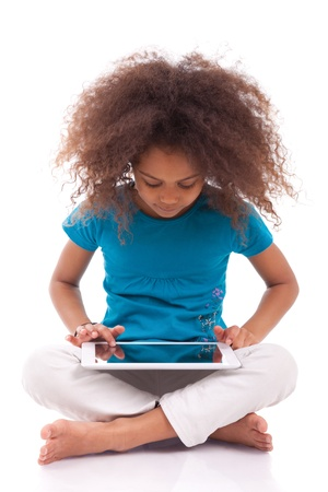 american children: Little african asian girl using a tablet  pc, isolated on white background