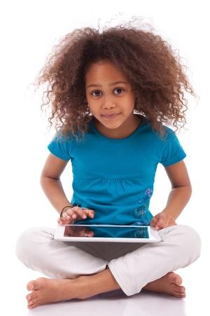 ni�os africanos: Peque�a muchacha asi�tica africana con un Tablet PC, aislado en fondo blanco Foto de archivo