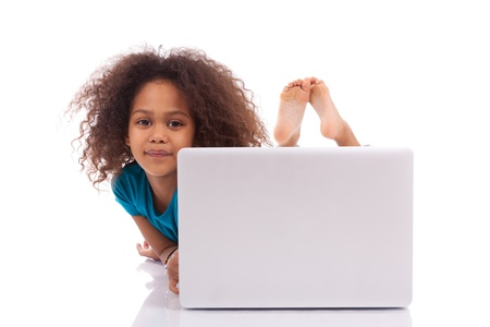 Little african asian girl using a laptop, isolated on white background photo