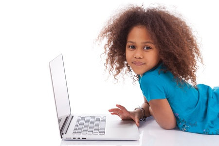 curly hair child: Little african asian girl using a laptop, isolated on white background Stock Photo