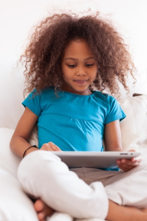 cute little girls: Little african asian girl seated on the couch using a tablet  pc Stock Photo