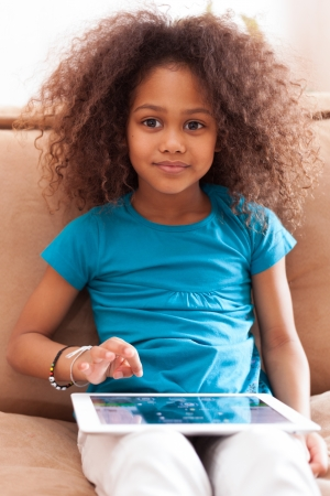afro american: Little african asian girl seated on the couch using a tablet  pc Stock Photo