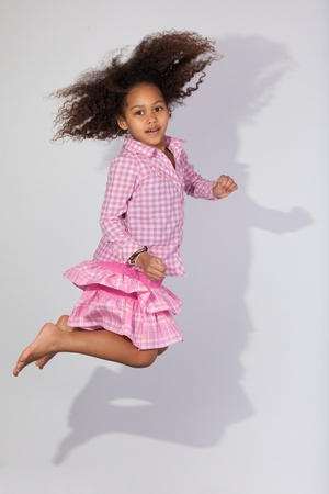 brazilian caribbean: Portrait of cute Young African American girl jumping, over gray background