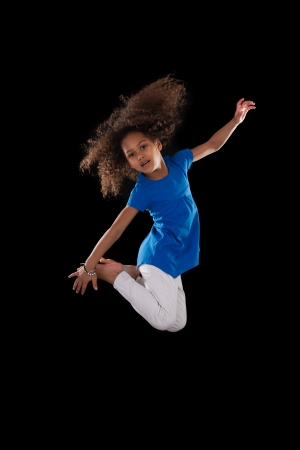 Portrait of cute Young African American girl jumping, over black background photo