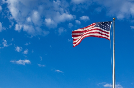 july: American flag - star and stripes floating over a cloudy blue sky Stock Photo