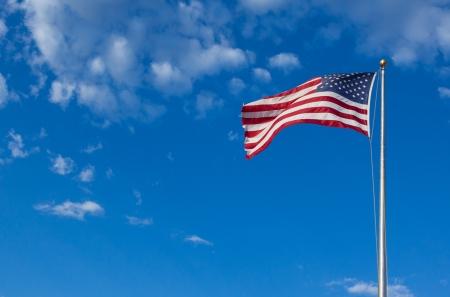 julio: Bandera de Estados Unidos - estrella y rayas que flotan sobre un cielo azul nublado