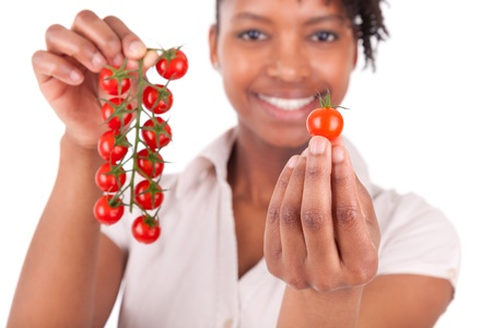 Young happy black  african american woman holding tomatoes, isolated on white background photo