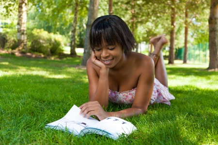 Outdoor portrait of young african american woman lying down on the grass reading a book photo