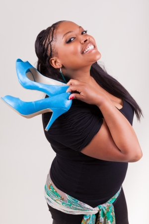 plus sized: Portrait of a young beautiful black woman holding a pair of  shoes