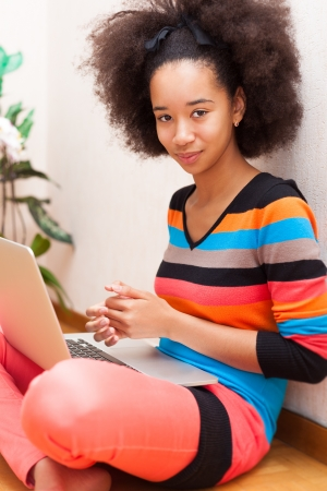 curly hair child: Black African American teenage girl with a afro haircut seated on the floor using a laptop computer Stock Photo