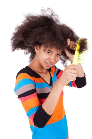 Black African American teenage girl combing her afro hair, isolated on white background photo