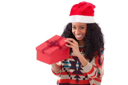 Young black African American woman wearing a santa hat opening a gift box, isolated on white background photo