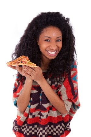 afro caribbean: Young black african american teenage girl eating a slice of pizza, isolated on white background - african people