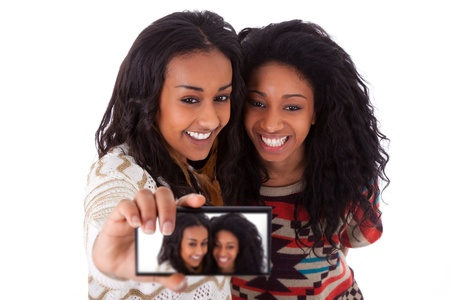 telephone together: Young black african american teenage girls taking pictures with cell phone, isolated on white background - african people