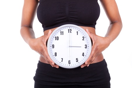 'flat stomach': Young black african american woman holding a clock in front of her belly, isolated on white background - African people