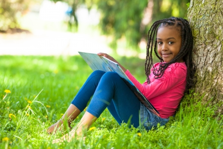 education kids: Outdoor portrait of a cute young black little  girl reading a book - African people Stock Photo