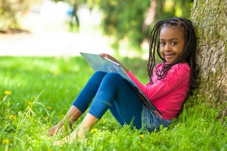 ni�os en la escuela: Retrato al aire libre de una joven ni�a negro lindo que lee un libro - los africanos Foto de archivo