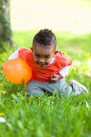 Outdoor portrait of a cute young  little black boy playing with a balloon - African people photo