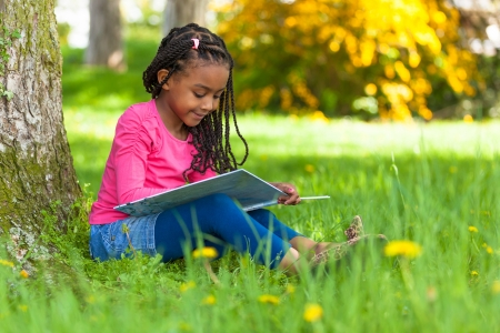 child food: Outdoor portrait of a cute young black little  girl reading a book - African people Stock Photo