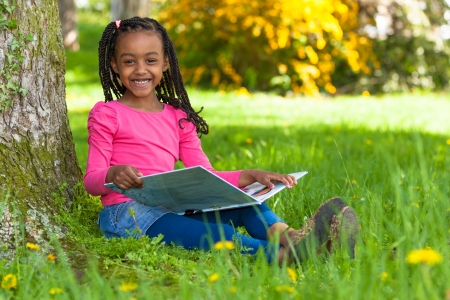 Outdoor portrait of a cute young black little  girl reading a book - African people Foto de archivo