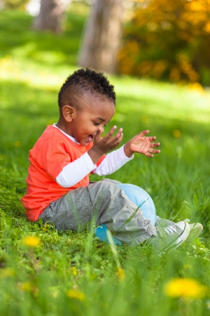 ethnic children: Outdoor portrait of a cute young  little black boy playing with a balloon - African people