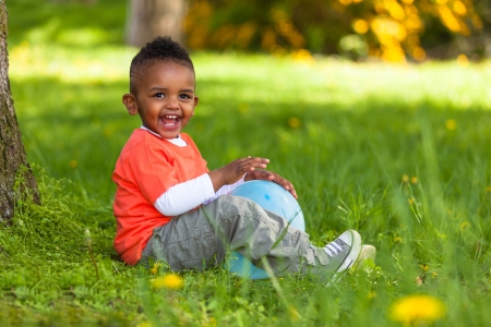 south african: Outdoor portrait of a cute young  little black boy playing with a balloon - African people