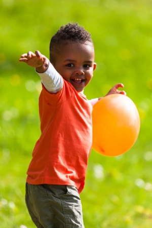 afro american: Outdoor portrait of a cute young  little black boy playing with a balloon - African people
