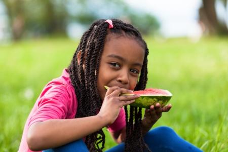 ni�os comiendo: Retrato al aire libre de una joven ni�a negro lindo que come la sand�a - pueblo africano Foto de archivo