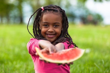 diversity children: Outdoor portrait of a cute young black little  girl eating watermelon - African people Stock Photo