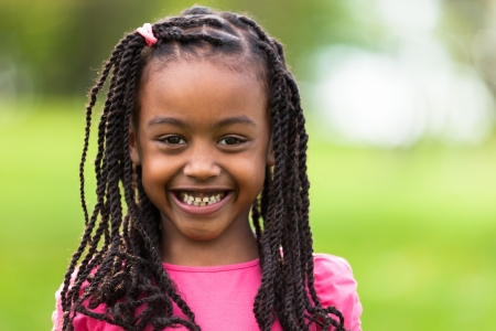 braid: Outdoor close up portrait of a cute young black girl smiling - African people Stock Photo